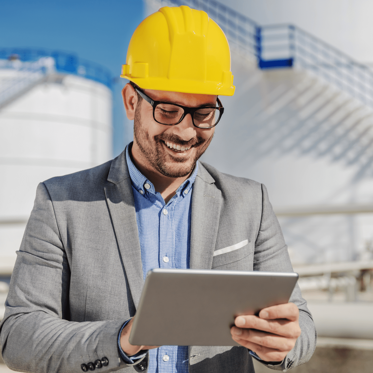 Oil foreman looking at tablet in front of oil containers